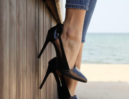 Woman in heels sitting on ledge by the sea
