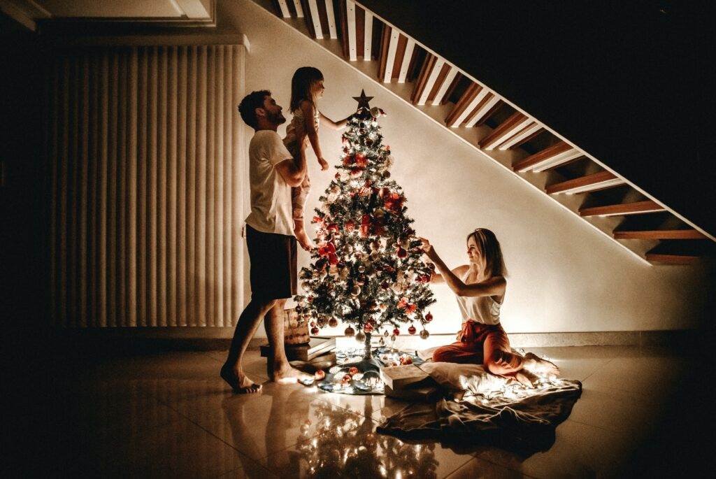 Stepmother decorating the Christmas tree with her stepfamily